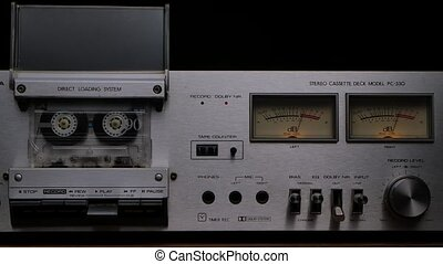 Vintage cassette player deck from 80s. Stereo recorder with rotating cassette, controls, dashboard and buttons on black studio background. Close up. Slow motion