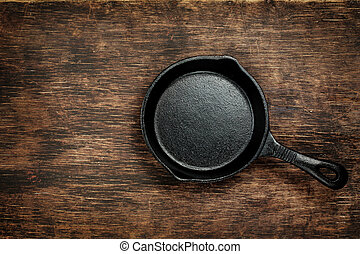 Vintage cast iron skillet on rustic wood background. Food ...