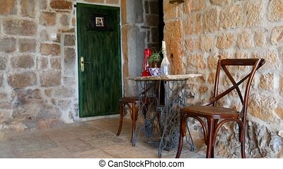 Vintage chairs and a table, against the backdrop of a stone...
