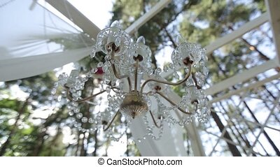 Vintage chandelier hanging in the street among white fabrics...