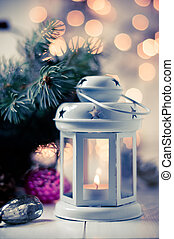 Vintage Christmas decor, old Christmas decorations, lanterns, garlands and spruce branches on a white table. Retro colors