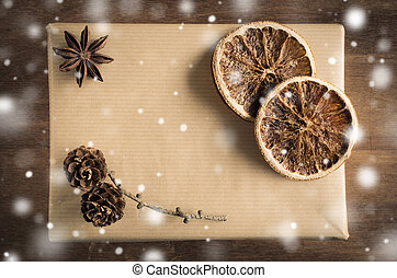 Vintage Christmas Kraft Gift Box in Rustic Style Decorated with Cones and Dried Orange Slices. Snow Falling Effect.