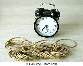 Vintage clock and rope on table