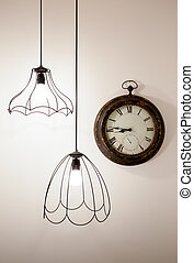 Vintage clock on a white wall with stylish lamps