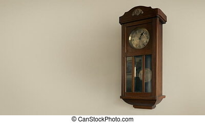 Looped shot of old manual wall clock with pendulum moving back and forth