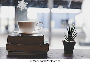Vintage color Cup of coffee with book in coffee shop.