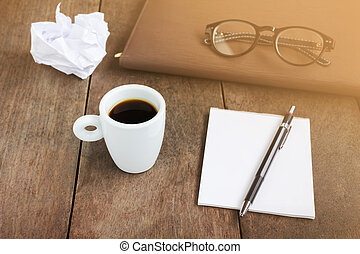 white cup of black coffee with blank note book and pencil