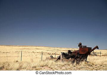 vintage combine harvester and old field of rye, Arizona, USA