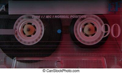 Vintage compact audio cassette extreme close up. Retro music cassette in the rewinds illuminated by red neon lights. Slow motion