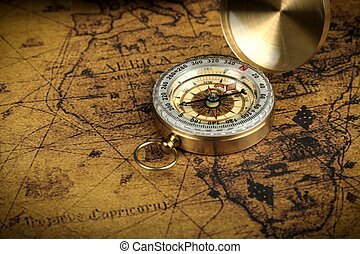 Vintage Compass lies on an ancient world map - adventure stories background