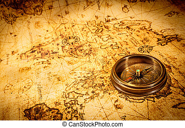 Vintage compass lies on an ancient world map. - Vintage...