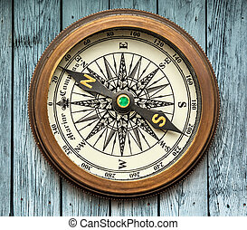Vintage compass on wooden background in closeup