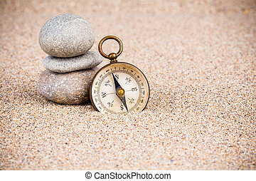 Vintage compass with pebble stones on sand
