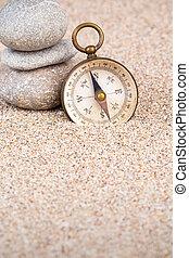 Vintage compass with three pebble stones portrait view