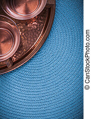 Vintage coppery tray and tea cups on blue table cloth