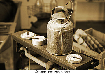 Old-time milk/cream can atop an antique scale with weights in an authentic historical Creamery setting (vintage tone and grain - shallow focus).