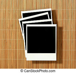 Vintage Crooked Old Polaroid Film Blanks Lying on Bamboo Background