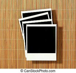 Vintage Crooked Old Polaroid Film Blanks Lying on Bamboo Background