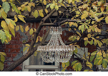 Vintage crystal chandelier hanging from a tree branch on the background of an old shabby building, street image. Retro chandelier with crystal. Selective focus