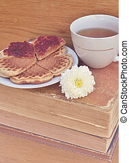 Vintage cup of tea with books and cookies