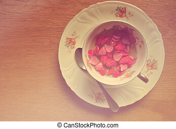 Vintage cup of tea with petals on wooden