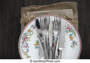Vintage cutlery and crockery on cloths on rustic wooden background