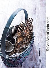 Vintage cutlery in old blue wicker basket