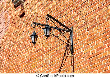 Vintage decorative lantern hanging on an old brick wall