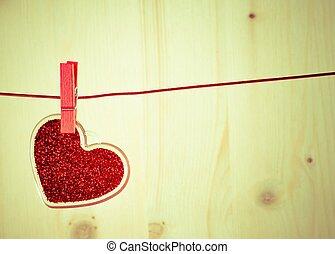 vintage decorative red heart hanging on wood background, concept of vintage valentine day