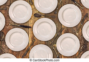 Vintage dinner plates, knives, forks and spoons on an old table