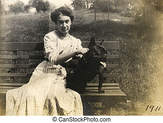 Vintage Dog Walker - Vintage portrait of a young woman and...