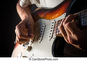Vintage electric guitar closeup, male hands playing with a...