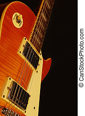 Vintage electric jazz guitar closeup on black background. Shallow depth of field.