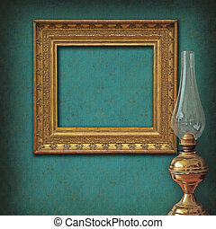 Vintage empty frame on damask wallpaper with antique oil lamp