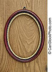 vintage empty oval picture art frame on oak plank