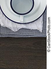 Vintage enamelware crockery on retro cloths on rustic wooden background