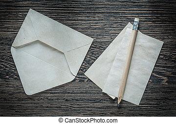 Vintage envelope blank paper sheet pencil on black board