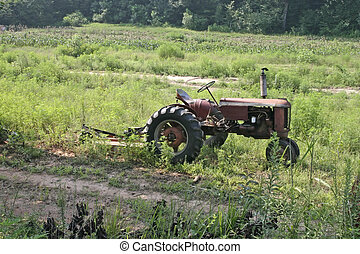 vintage farming tractor on sloped field
