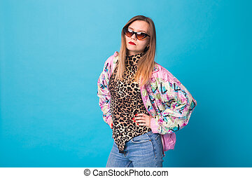 Vintage fashion look concept - pretty young woman wearing a retro jacket and leopard body on blue background