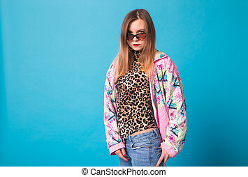 Vintage fashion look concept - pretty young woman wearing a retro pink jacket and leopard body on blue background