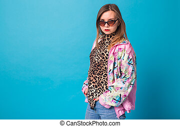 Vintage fashion look concept - pretty young woman wearing a retro pink jacket and leopard body on blue background with copy space