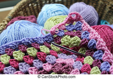 Vintage feel crochet, the making of an afghan blanket, with wool in a basket