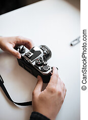 Vintage film camera in the man hands on a white background