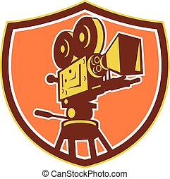 Illustration of a vintage movie film motion-picture camera viewed from low angle set inside shield crest on isolated background done in retro style.