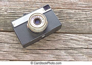 Vintage film photo camera on wooden background