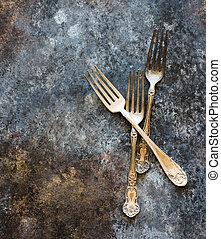 Vintage forks on rustic dark background