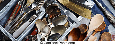 Vintage forks, spoons and knives in a dark old wooden box on a gray concrete or stone background. Selective focus.Top view. Copy space