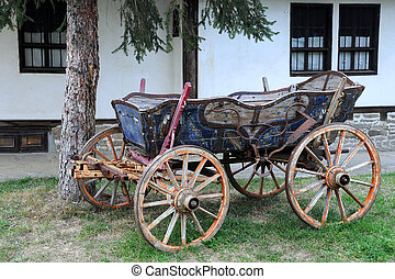 Vintage wooden four-wheeled cart against the background of traditional Bulgarian house wall