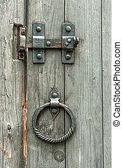 Vintage gate valves and old wooden gates with round metal handles in the form of rings.