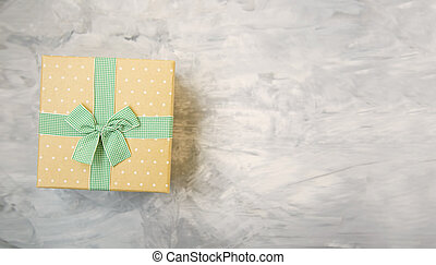 Vintage gift box with ribbon and bow on concrete gray background